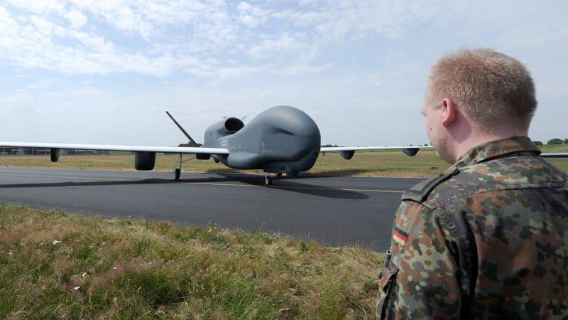 Ein männlicher Bundeswehrsoldat steht vor einer Drohne.